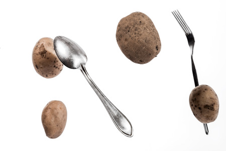 levitation: Brown potato tubers, spoon and fork flying in the air. Isolated image on white background.