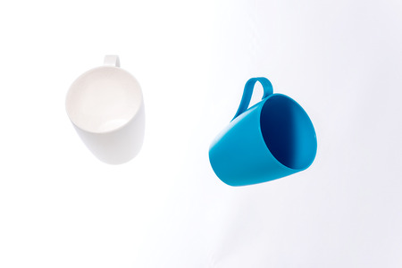 weightless: Pair of white and blue mugs of plastic hovering in the air. Isolate on white background.