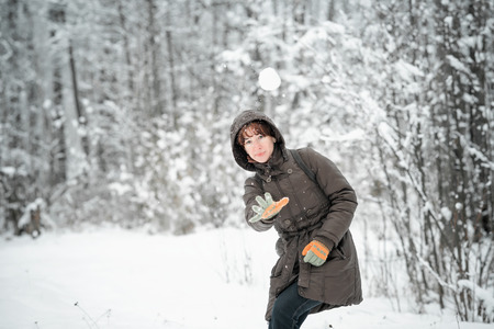non urban: Young woman in hood throws a snowball towards the viewer.