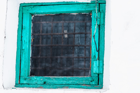 gaol: The window in a wooden frame with glass and bars inside.