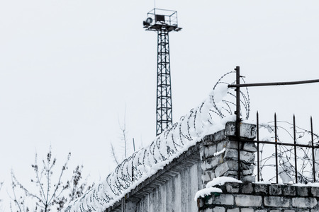 gaol: Fence with barbered wire on the sky background in winter. Stock Photo