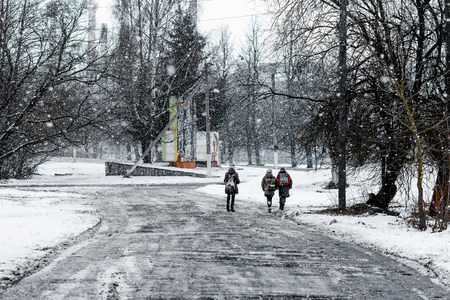 non urban: The girls are going fron the school on the village street during a snowfall .