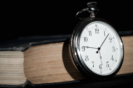 transience: Closeup of steel pocket watch on old book over black background. Stock Photo