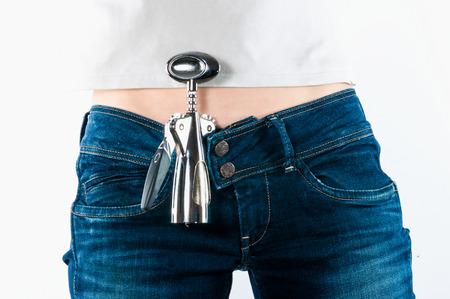 alcoholismo: Sacacorchos detr�s de un cintur�n de los pantalones vaqueros de las mujeres. El concepto de alcoholismo hembra.