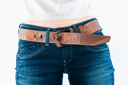buckle: Wide leather belt with a buckle on female blue jeans .