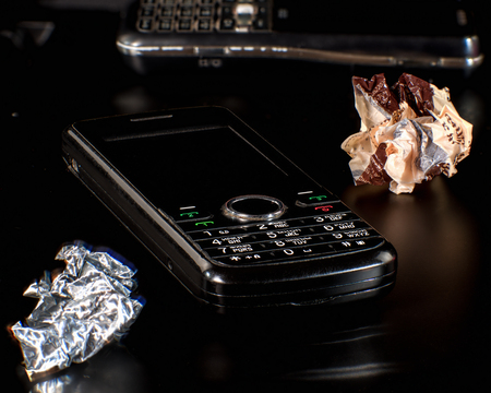 transience: Old mobile phones with paper waste. The concept of rapid obsolescence of gadgets and the transience of fashion . Stock Photo