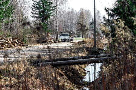 logging truck: Logging truck near sawmill standing around in the village street .