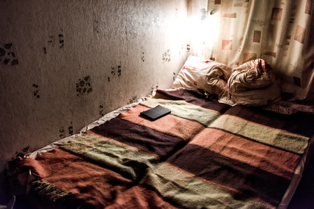 unmade: Night-lighted corner of the room with unmade double bed in warm colours.