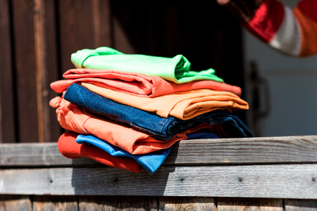 parapet wall: Stack of colourful garment on the wooden parapet. Stock Photo