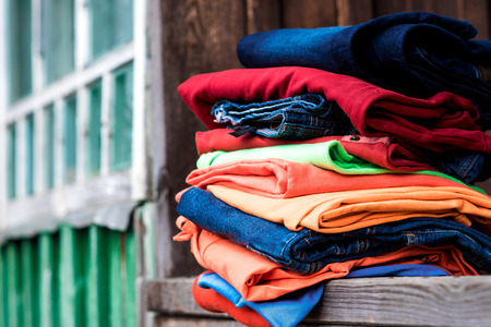 parapet: Stack of colourful garment on the wooden parapet. Stock Photo