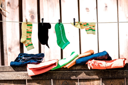 parapet wall: Bright socks drying on the clotheline outdoors.