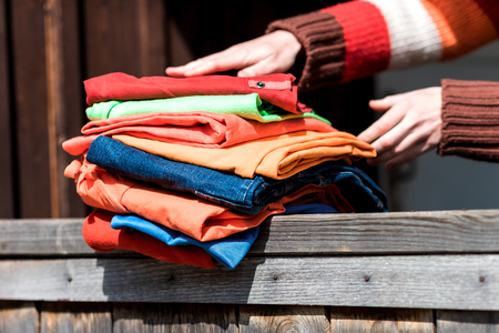 parapet: Female hands holding stack of clothing on wooden parapet.