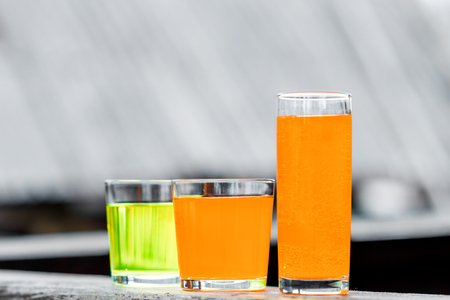 yellow to drink: Glasses of orange and yellow drink on the wooden surface.
