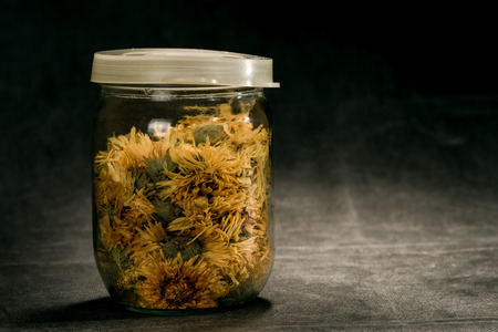 officinal: Dried flowers of calendula officinalis in closed glass container.