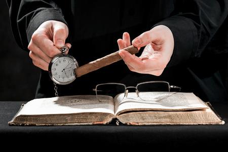 sotana: Las manos humanas en sotana negro que llevaban el cigarro y el reloj por encima del libro.
