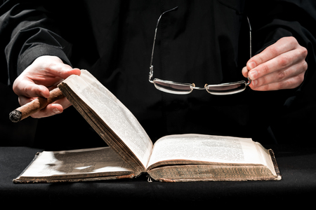 cassock: Human hands in black cassock carrying the cigar and eyeglasses above the book.