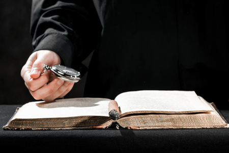cassock: Human hands in black cassock carrying the pocket watch above the book.