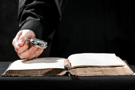 sotana: Las manos humanas en sotana negro que lleva el reloj de bolsillo por encima del libro.