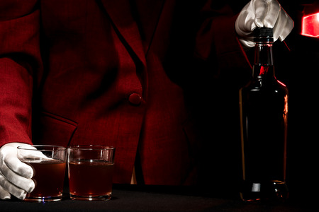 barmen: Human hands in white gloves above the bar counter with the bottle and glasses of alcohol.