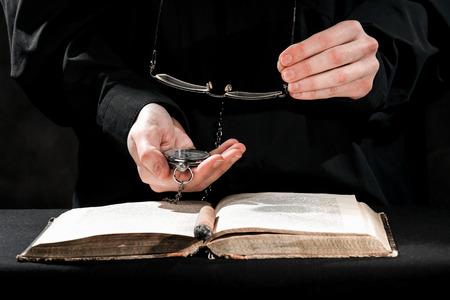 sotana: Las manos humanas en sotana negro que lleva las gafas y mirar por encima del libro. Foto de archivo