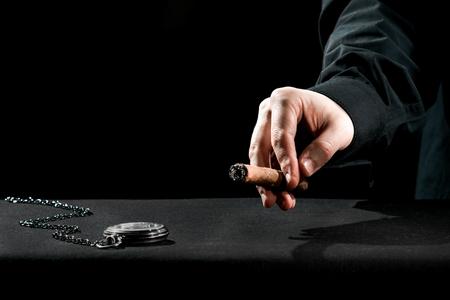 cassock: Human hands in black cassock carrying the cigar near the watch.
