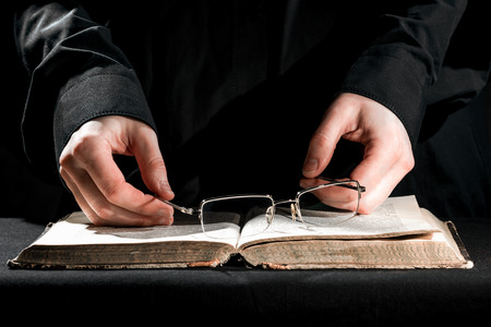 garb: Human hands in black cassock carrying the eyeglasses above the book. Stock Photo