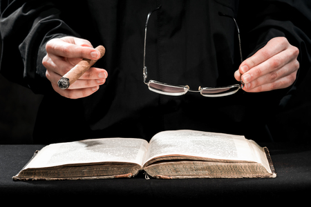 garb: Human hands in black cassock carrying the cigar and eyeglasses above the book.