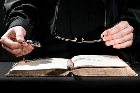 cassock: Human hands in black cassock carrying the glasses and watch above the book. Stock Photo