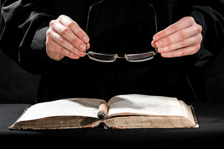 sotana: Human hands in black cassock carrying the cigar and eyeglasses above the book.