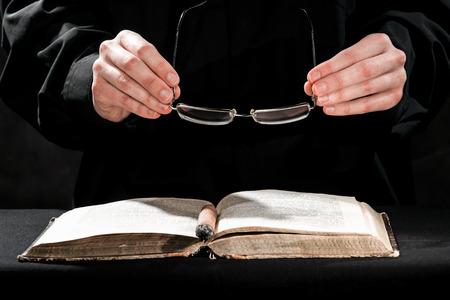 sotana: Las manos humanas en sotana negro que llevaban el cigarro y las gafas por encima del libro.