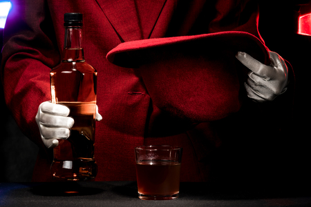 bowler: Human hands in white gloves with the bowler hat and alcohol.