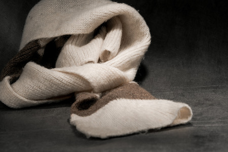 muffler: Knitted warm wool muffler on dark background. Stock Photo