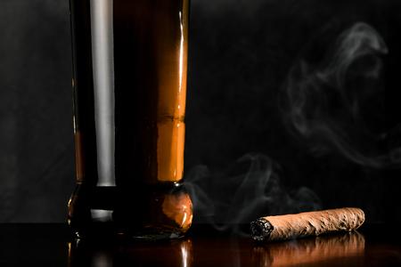 caoba: Fumar cigarros y una botella de whisky en una superficie oscura de madera de caoba. Foto de archivo