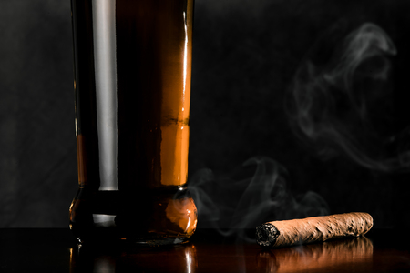 mahogany: Smoking cigar and bottle of whiskey on a dark surface of mahogany wood.