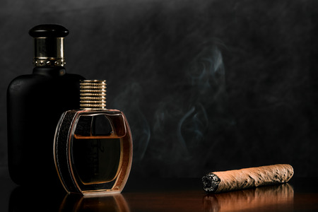 scent: Romantic pair of glass scent bottles and cigar on a dark surface of the noble wood.