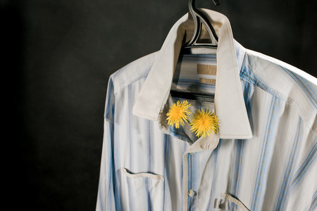 civility: Shirt hanging over dark background with dandelions behind the collar.
