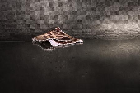 sudarium: Single napkin on reflecting surface over dark background.