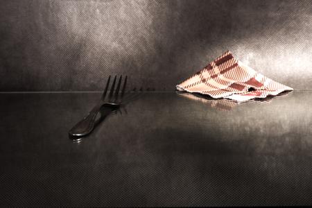 sudarium: Fork and napkin on reflecting surface over dark background.