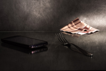 sudarium: Fork, cell phone and napkin on reflecting surface over dark background. Stock Photo