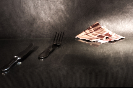 sudarium: Fork, table knife and napkin on reflecting surface over dark background.