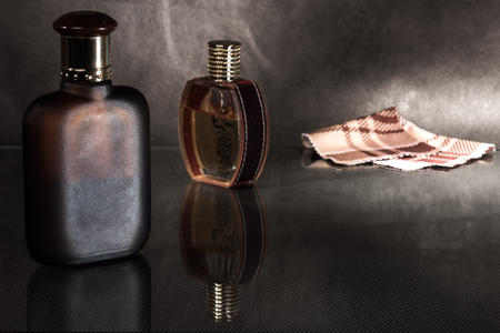 sudarium: Pair of glass scent bottles and napkin on a dark surface.