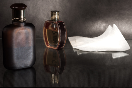 scent: Pair of glass scent bottles and napkin on a dark surface.