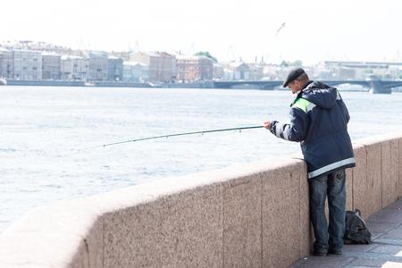 blagoveshchensky: St.Petersburg, Russia - May 16, 2016: man fishing on the Neva river over the background of Blagoveshchensky bridge.