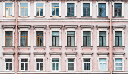 tilt views: Windows in rows on facade of old apartment building front view, St. Petersburg, Russia. Stock Photo
