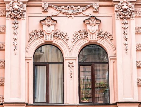 tilt views: Windows in row on facade of old apartment building front view, St. Petersburg, Russia.