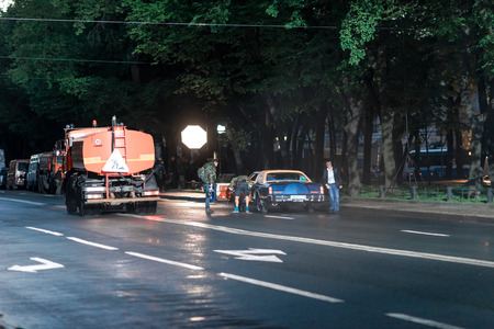 film crew: St. Petersburg, Russia - May 19, 2016: Film crew making a scene with car and street sweeper on location at the Konnogvardeysky boulevard on the night.