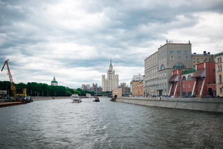kotelnicheskaya embankment: Moscow, Russia - June 5, 2016: One of Stalin skyscrapers - the house on Kotelnicheskaya Embankment. Touristic ships.