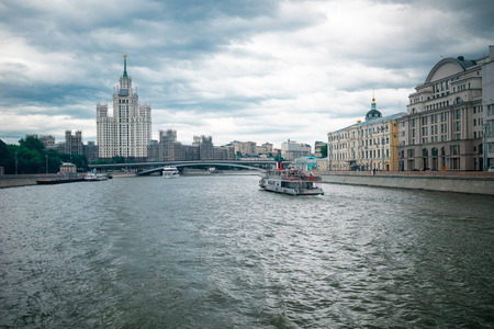 kotelnicheskaya embankment: Moscow, Russia - June 5, 2016: One of Stalin skyscrapers - the house on Kotelnicheskaya Embankment. Big Ustyinsky bridge. Touristic ships.