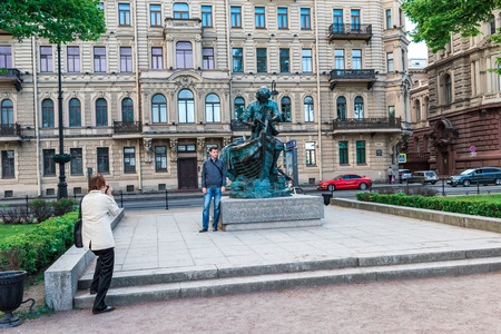 shipbuilder: St.Petersburg, Russia - May 17, 2016: Admiralty embankment. A woman taking photo of a man near Peter-shipbuilder monument.