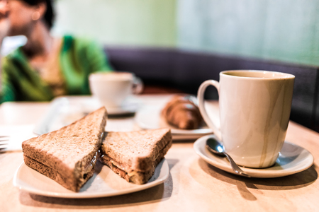 little table: Cups of tea or coffee, sandwiches and croissant on the little table.
